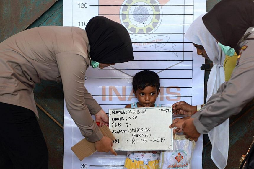 A Rohingya boy from Myanmar is photographed during an Indonesian police identification process at the confinement area in the fishing port of Kuala Langsa in Aceh province on May 18, 2015. -- PHOTO: AFP