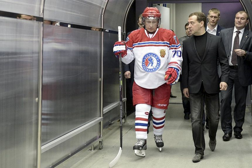 Russian Prime Minister Dmitry Medvedev (centre) speaking with President Vladimir Putin (left) during a gala match of the National Amateur Ice Hockey Teams' Festival organised by the Night Ice Hockey League in Sochi, Russia, on May 16, 2015. -- PHOTO: