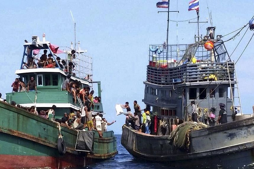 MAY 14: Migrants on the drifting vessel (left) reaching out for supplies from a Thai boat in the Andaman Sea, near the Malaysian border. The migrant boat was later turned back out to the Andaman Sea.