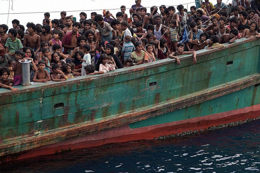 MAY 16: The migrant boat, tethered to a Thai navy patrol vessel, being towed back out to sea again. Migrants crammed in a boat adrift off the Thai island of Koh Lipe. Those aboard said they had been at sea for up to three months, but there was no res
