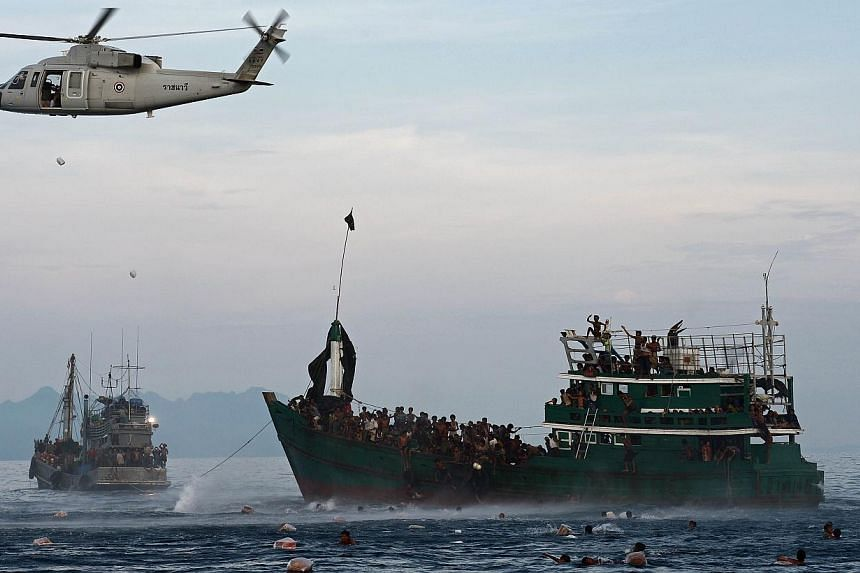 This file photo taken on May 14, 2015, shows Rohingya migrants swimming to collect food supplies dropped by a Thai army helicopter after they jumped from a boat (right) drifting in Thai waters off the southern island of Koh Lipe in the Andaman sea. -