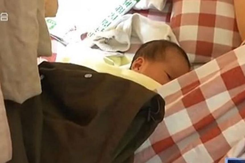 The baby girl in a hospital with her mother. She was born in the toilet of an Internet cafe in Nanchang, Jiangxi province, on May 11, 2015. -- PHOTO: SCREENGRAB FROM YOUKU.COM