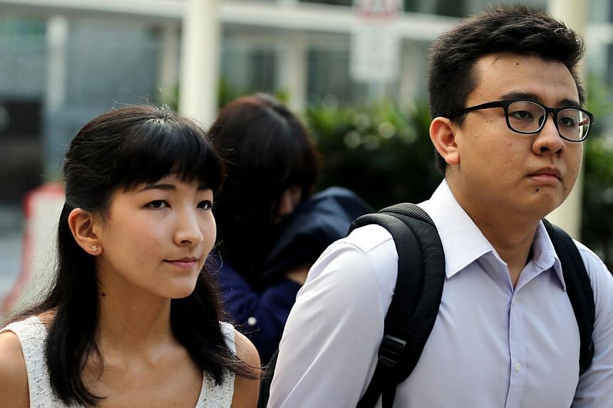 Court papers for a copyright infringement suit initiated by Singapore Press Holdings were served to Ai Takagi (left) and Yang Kaiheng (right), the couple behind sociopolitical website The Real Singapore, outside State Courts on May 18, 2015. -- ST PH