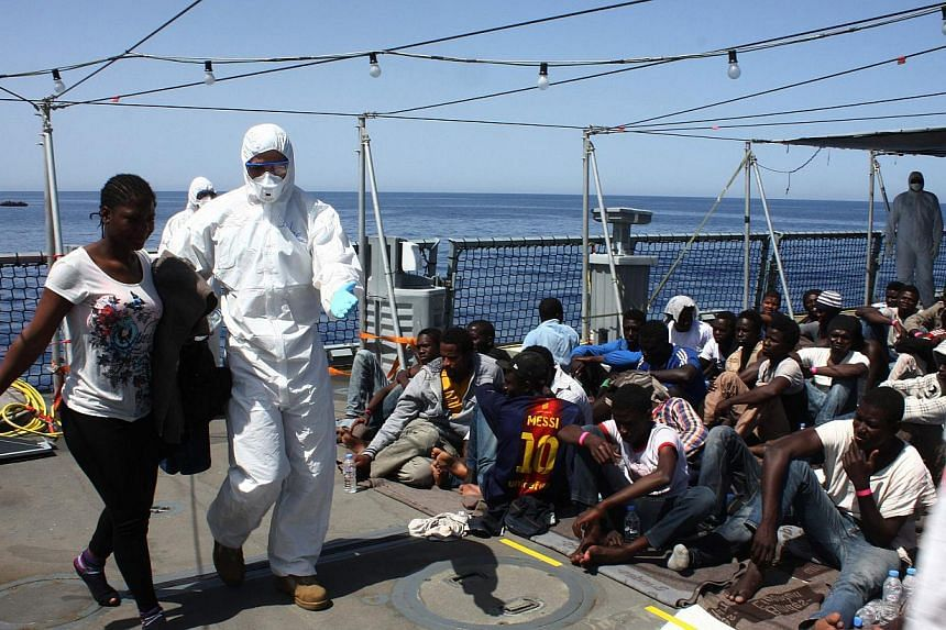 Migrants sit on board the German Navy frigate Hessen at sea in the Mediterranea off the Libyan coast, on May 14, 2015. European Union (EU) ministers are set to approve plans on Monday, May 18, for an unprecedented naval force to fight people smu