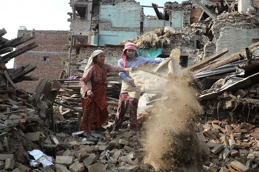 Nepalese earthquake survivors clear the rubble as they salvage belongings from a damaged house in devastated area of Bhaktapur, on the outskirts of Kathmandu, Nepal, on May 18, 2015.Nepal on Monday imposed a two-month moratorium on the start of