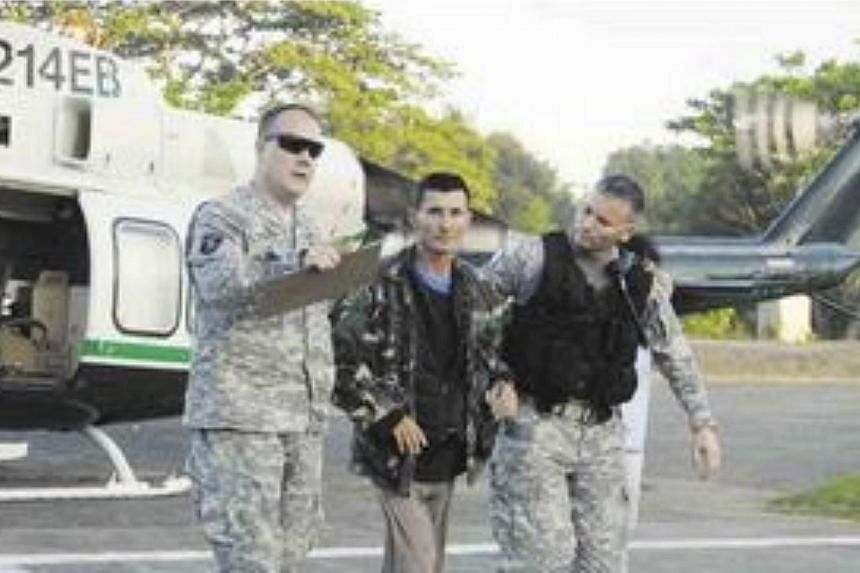 Australian Warren Rodwell (centre) after he was released by Abu Sayyaf militants on March 23, 2013. A Philippine policeman has been arrested over the kidnapping-for-ransom of Mr Roswell, police said on Monday, May 18, 2015. -- PHOTO: COURTESY OF WEST