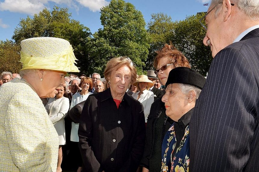 Britain's Queen Elizabeth II (left) talks to Holocaust survivors (left to right) Susan Pollock, her daughter Sandra Gee, Cirla Lewis, also a survivor and her husband Phillip Lewis during a garden party held at Buckingham Palace, in London on May 12.