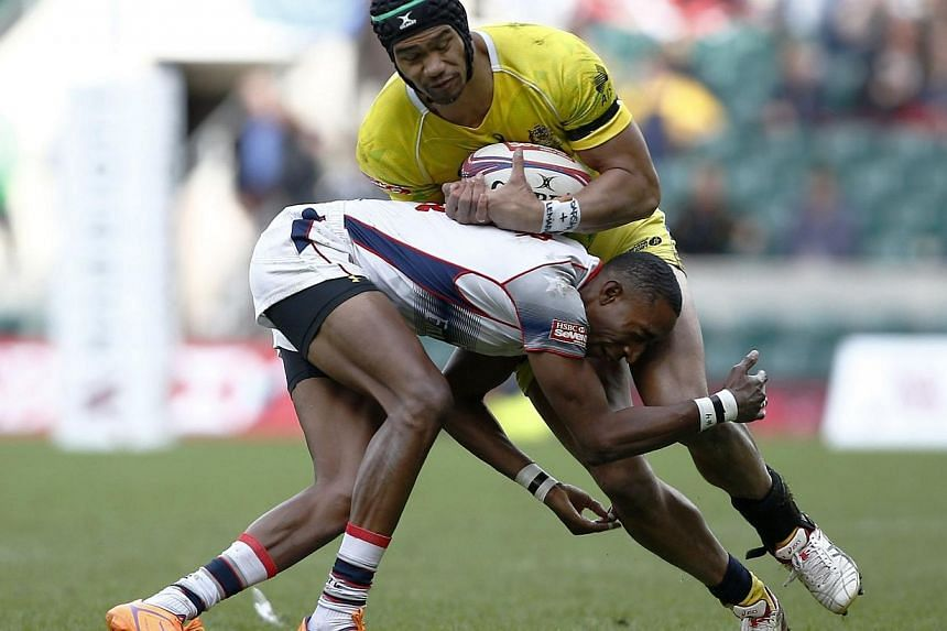 Perry Baker (left) of the United States tackles Australia's Pama Fou during the London Sevens rugby union cup final match between USA and Australia, part of the IRB Sevens World Series, at Twickenham Stadium in London on Sunday. -- PHOTO: AFP