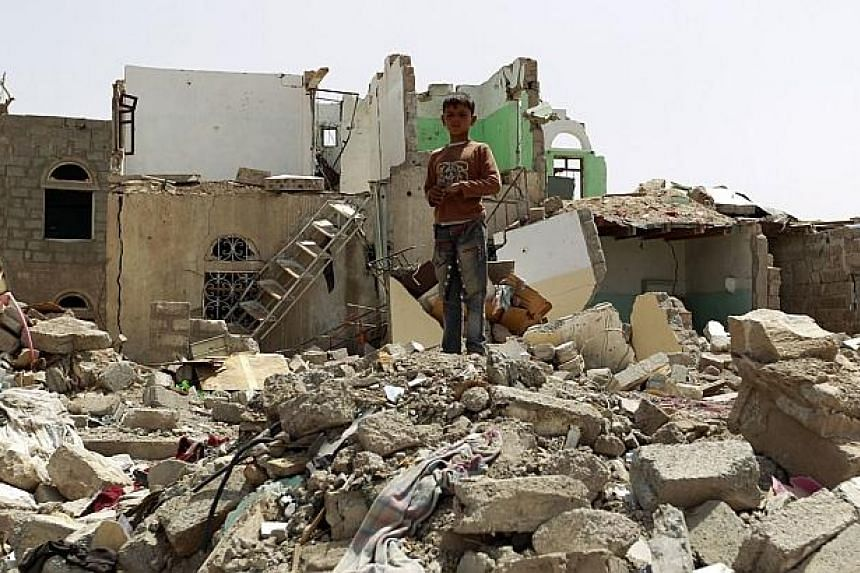 A Yemeni boy stands amidst the rubble of houses destroyed by Saudi-led air strike on a residential area last month, in the capital Sanaa, on Monday. Saudi-led coalition warplanes resumed strikes on rebel positions in southern Yemen after a five