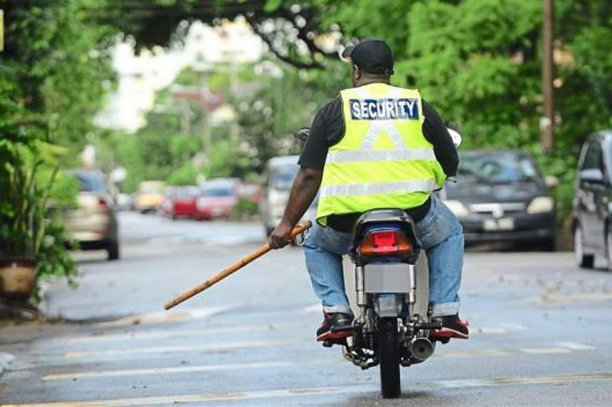 A motorcycle-riding security guard patrolling a neighbourhood street in Malaysia. -- PHOTO: THE STAR/ASIA NEWS NETWORK