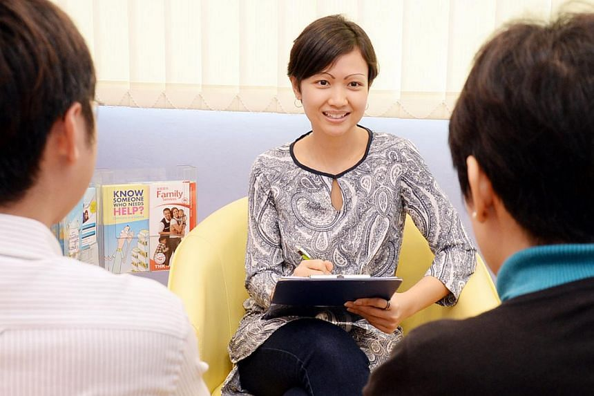 Ms Nurfizah Mohd Noor works a social worker and manages over 40 cases of clients or families who need help at the Family Service Centre (FSC) Thye Hua Kwan (THK) in Jurong. -- PHOTO: BERITA HARIAN FILE