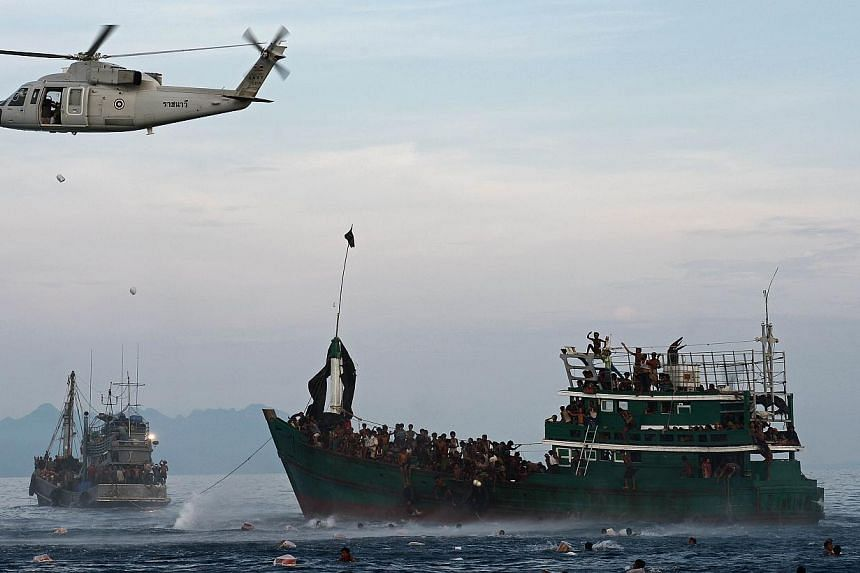 Rohingya migrants swimming to collect food supplies dropped by a Thai army helicopter after they jumped from a boat (right) drifting in Thai waters off the southern island of Koh Lipe in the Andaman sea on May 14, 2015. -- PHOTO: AFP