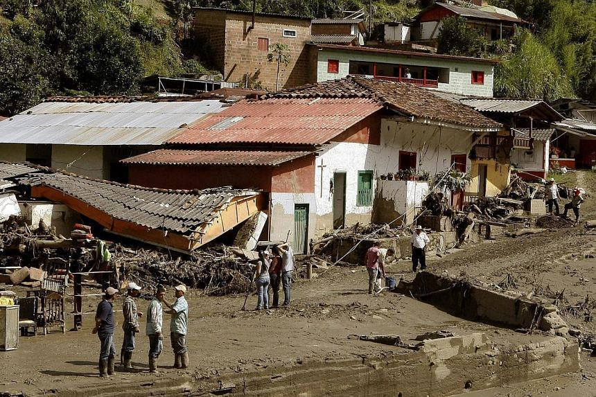 Inhabitants and rescue workers searching for victims of a landslide in Salgar municipality, Antioquia department, Colombia, on May 18, 2015. -- PHOTO: EPA
