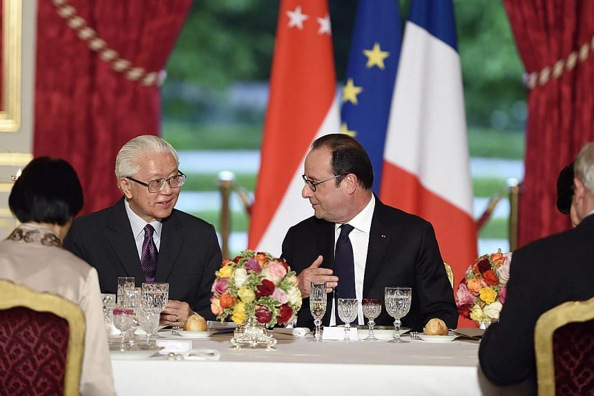 French president Francois Hollande (centre, right) speaking with President Tony Tan Keng Yam (centre, left) during an official dinner in his honour at the Elysee presidential Palace in Paris, France on May 18, 2015. -- PHOTO: EPA