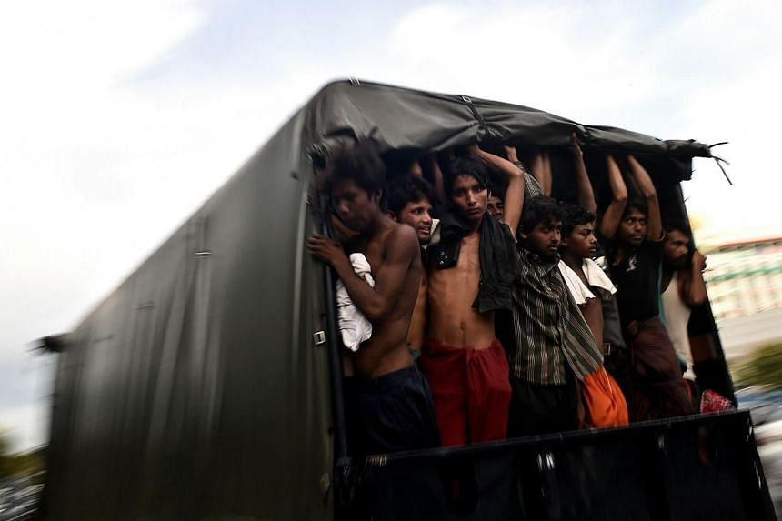 Bangladeshi migrants standing in a moving police van at the police headquarters in Langkawi on May 11, 2015. -- PHOTO: AFP