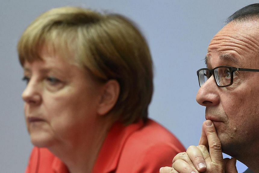German Chancellor Angela Merkel (left) and French President Francois Hollande attend the Petersberg Climate Dialogue conference in Berlin, Germany onMay 19, 2015. -- PHOTO: REUTERS