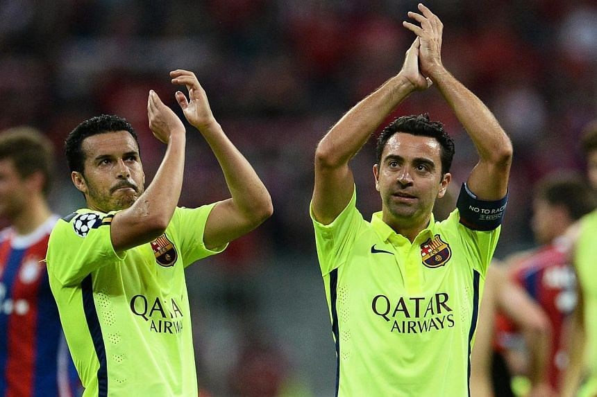 FC Barcelona players Xavi Hernandez (right) and Pedro Rodriguez (left) applaud supporters after the UEFA Champions League semi final second leg football match between FC Bayern Munich and FC Barcelona in Munich, Germany on May 12, 2015. -- PHOTO