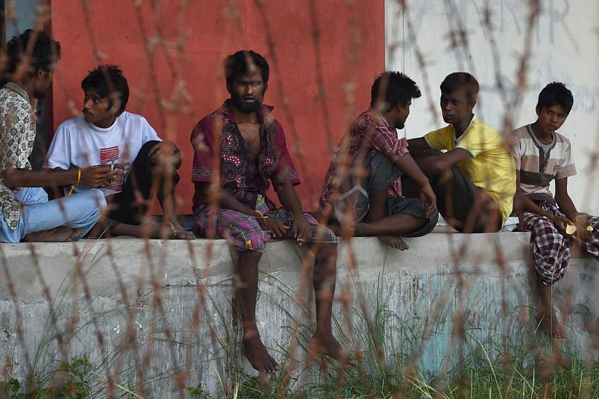 Rescued migrants from Bangladesh rest at the confinement area in the fishing port of Kuala Langsa in Aceh province on May 17, 2015. -- PHOTO: AFP