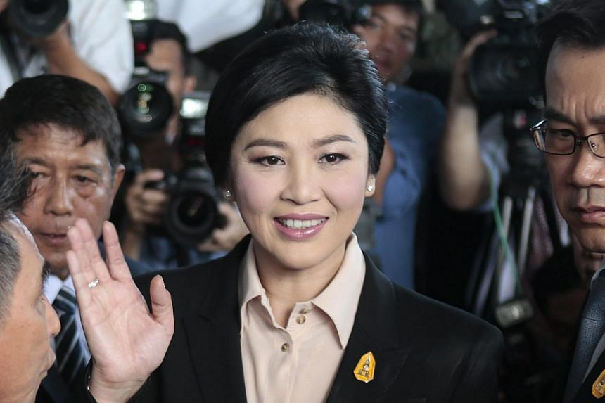 Thailand's ousted prime minister Yingluck Shinawatra (centre) greeting well-wishers and supporters as she arrives at the Supreme Court to face charges of corruption over a rice subsidy plan, in Bangkok, on May 19, 2015. -- PHOTO: EPA