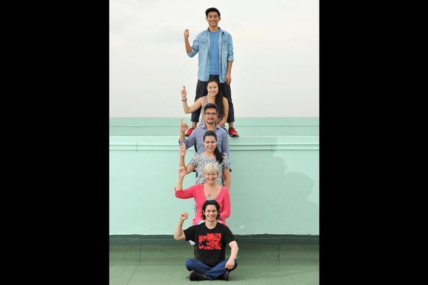 Cast of Tribes spelling the play's title by sign language: (from top) Thomas Pang, Ethel Yap, Adrian Pang, Frances Lee, Susan Tordoff and Gavin Yap. -- PHOTO: LIM YAOHUI FOR THE STRAITS TIMES