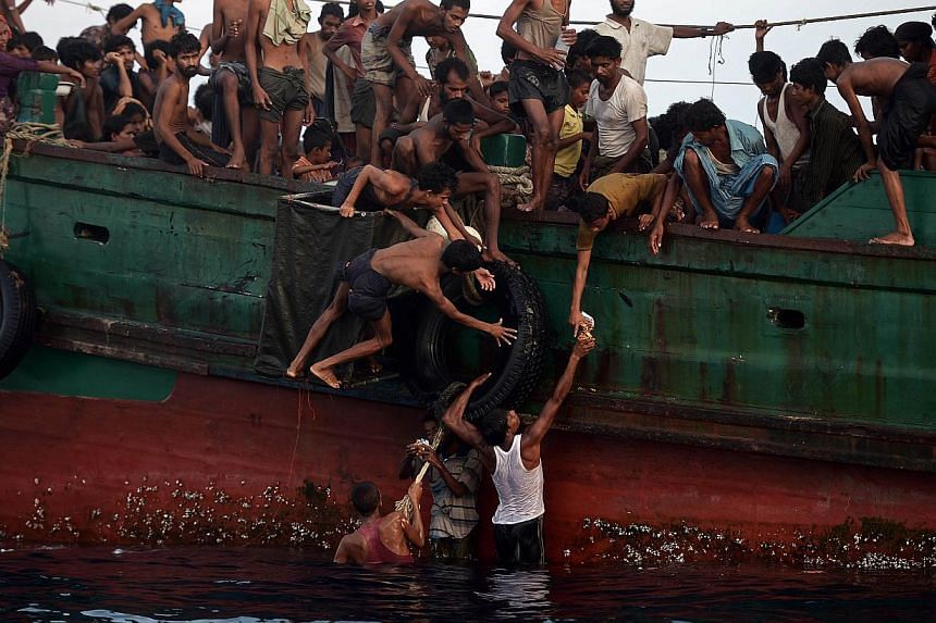 Rohingya migrants passing food supplies dropped by a Thai army helicopter to others aboard a boat drifting in Thai waters off the southern island of Koh Lipe in the Andaman sea on May 14, 2015. -- PHOTO: AFP