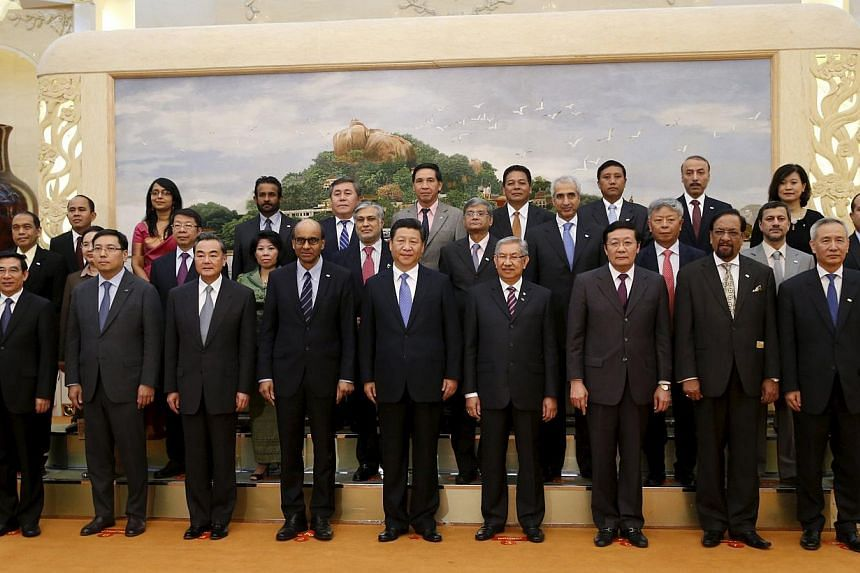 China's President Xi Jinping (centre) posing for photos with guests at the Asian Infrastructure Investment Bank launch ceremony at the Great Hall of the People in Beijing, on Oct 24, 2014. -- PHOTO: REUTERS