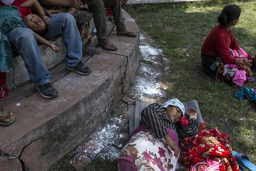 Maya Tamang, 20, sleeps next to her one-day-old daughter at a makeshift shelter outside Bhaktapur hospital in Bhaktapur, Nepal, May 13, 2015. -- PHOTO: REUTERS