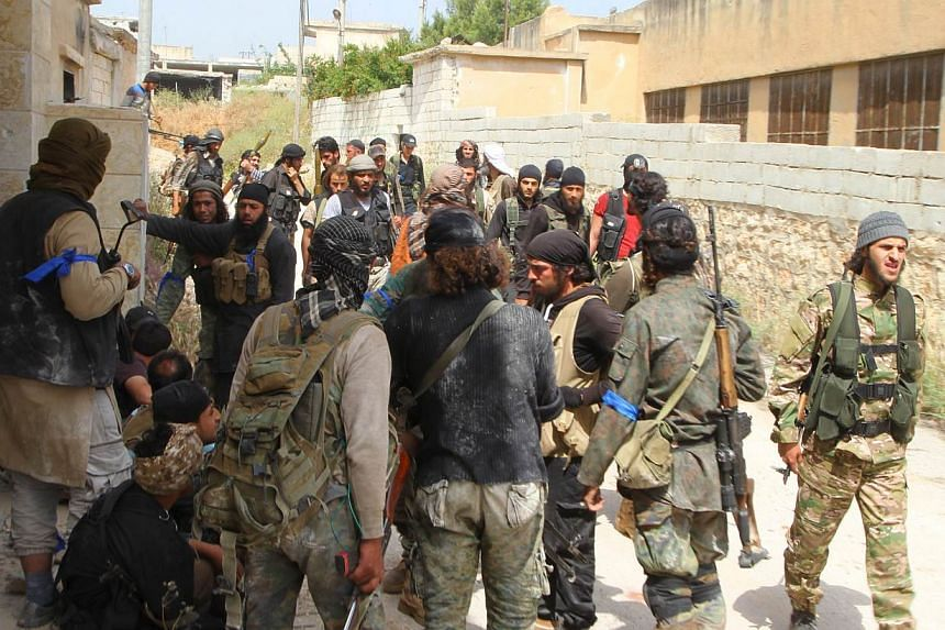 Rebel fighters gather in Mastouma village, after they said they had advanced on the area, in Idlib city, on May 19, 2015.A rebel coalition including Al-Qaeda's local affiliate seized the Syrian regime's largest remaining military base in Idlib