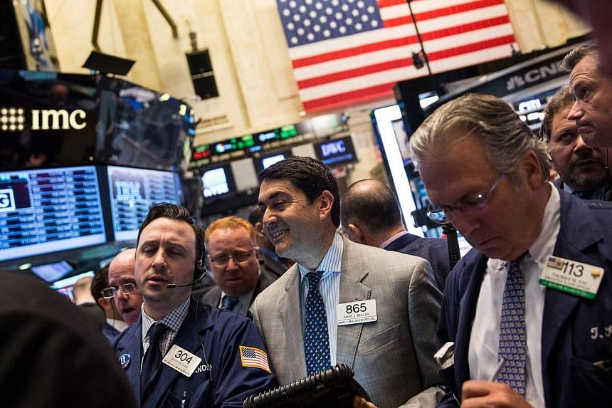 Traders work on the floor of the New York Stock Exchange in New York City. -- PHOTO: AFP