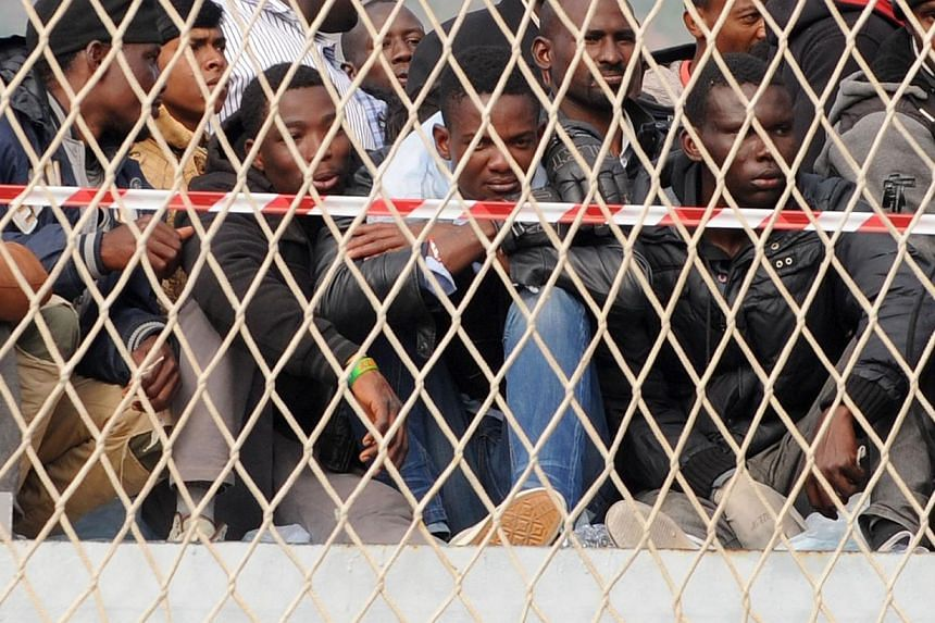 """Migrants wait to disembark from military ship """"Bettica"""" following a rescue operation at sea on May 5 in the port of Salerno in southern Italy.-- PHOTO: AFP"""