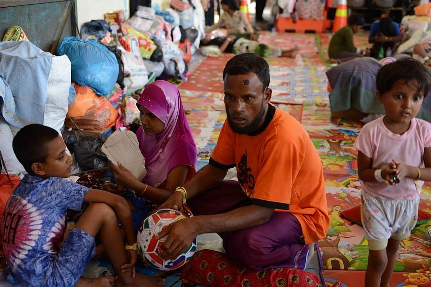 Rescued Rohingya migrant from Myanmar, Mohammad Amih (C), sits with other survivors at the port in Langsa in Aceh. A vicious fight among Rohingya and Bangladeshi migrants on board a foundering vessel off Indonesia left at least 100 dead, survivors sa