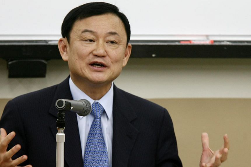 """Thailand's fugitive former prime minister Thaksin Shinawatra said on Tuesday he had no plans to mobilise his """"red shirt"""" supporters, but called the first year of the junta government that came to power in a coup """"not so impressive"""". -- PHOTO:BL"""