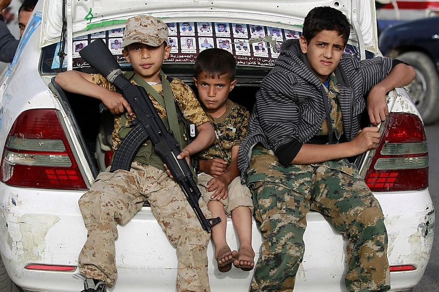Yemeni children, one holding a weapon, sit in a car boot during a march of supporters of the Shiite Huthi movement in the capital Sanaa in protest to the Saudi-led military operations against positions held by them and their allies, on May 18, 2015.
