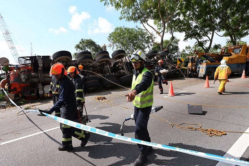 A trailer toppled on its left on a filter road on Airport Boulevard towards PIE heading to the city. The driver of the trailer, who was trapped inside the vehicle, was rescued at about 10.20am and taken to the hospital. -- ST PHOTO: NEO XIAOBIN