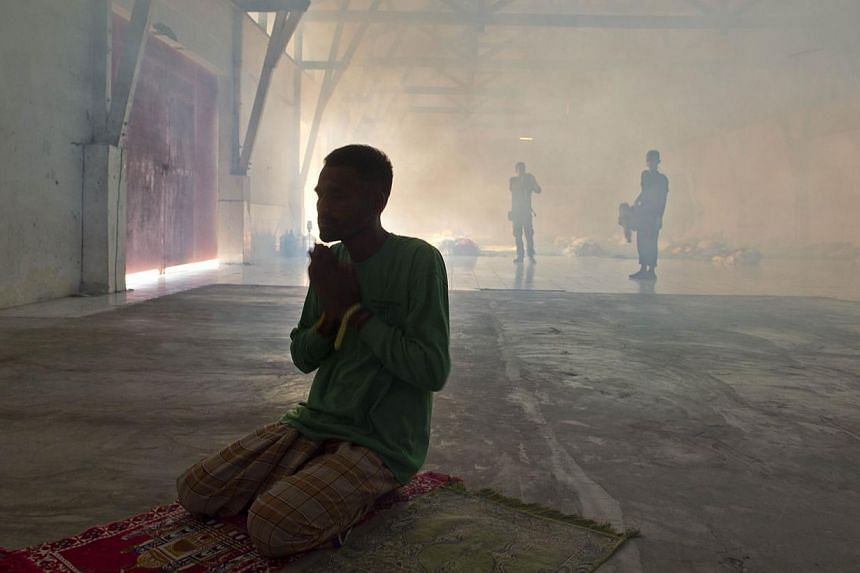 A rescued Bangladeshi migrant praying while Indonesian personnel fumigate a warehouse converted into sleeping quarters for migrants at a fishing port in Langsa, Aceh province, on May 19, 2015. The Philippines has said it is ready to accept migrants f