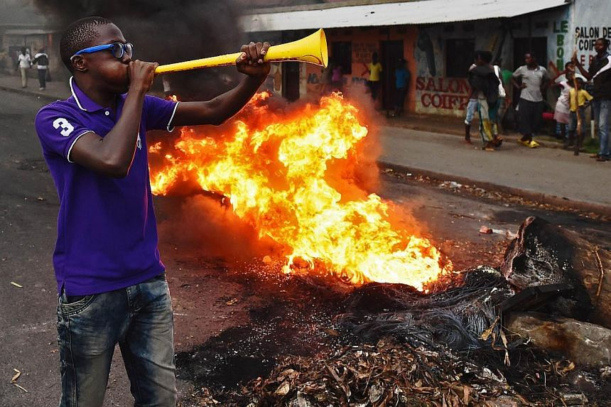 Protestors opposed to the Burundian president Pierre Nkurunziza's third term in office gather by a burning barricade during a demonstration in the Cibitoke neighbourhood of Bujumbura on May 19, 2015. Burundian security forces fired shots and tear gas