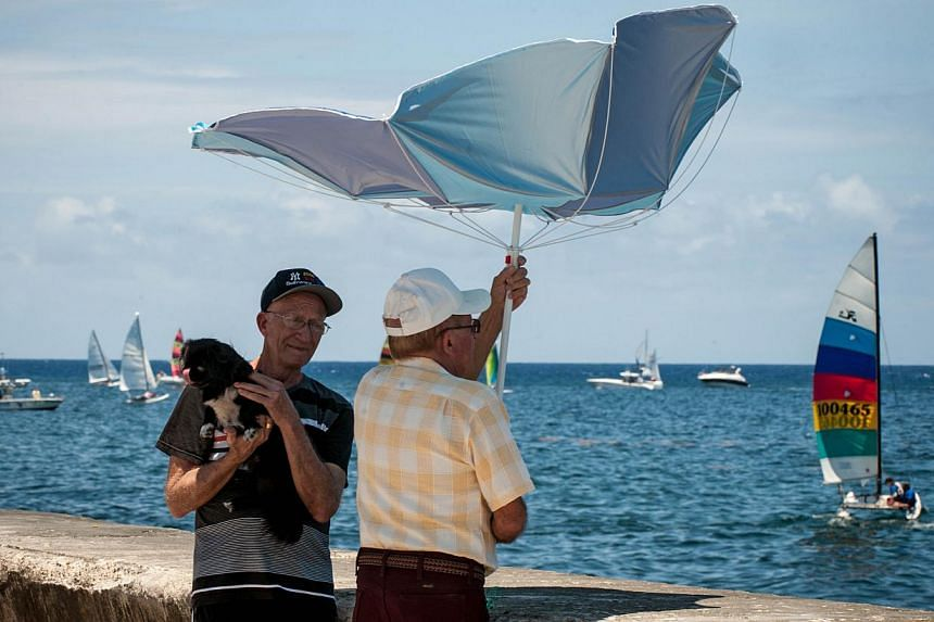 Men watching the Havana Challenge regatta in Havana on May 19, 2015. It is the first regatta since the two countries' decision to seek normal ties after more than five decades of Cold War strains. -- PHOTO: AFP