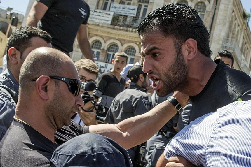 """Palestinian demonstrators are confronted by Israeli police during the Israeli """"flag march"""" through Damascus Gate in Jerusalem's old city during celebrations for Jerusalem Day on May 17, 2015. Two Israeli policemen were wounded in annexed east Jerusal"""
