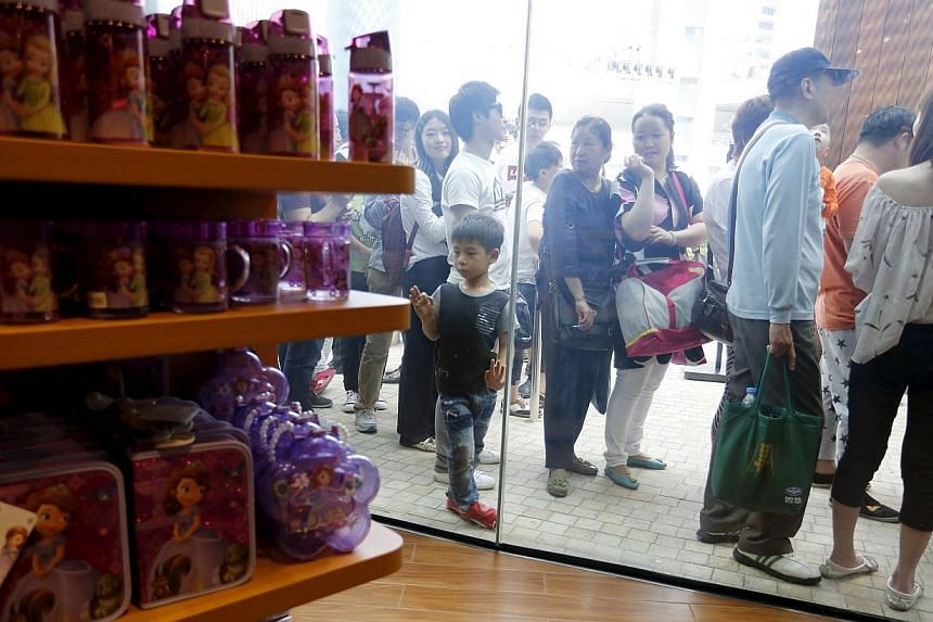 People queue to enter China's first Disney store at Pudong financial district in Shanghai on May 20, 2015. -- PHOTO: REUTERS