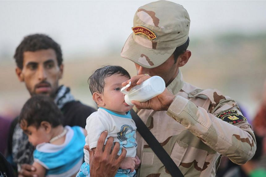 An Iraqi soldier carrying a displaced child from Ramadi on the outskirts of Baghdad on May 19, 2015. US President Barack Obama weighed faster training and arms supplies for Iraqi tribes on Tuesday, while eyeing a rapid counteroffensive to retake Rama