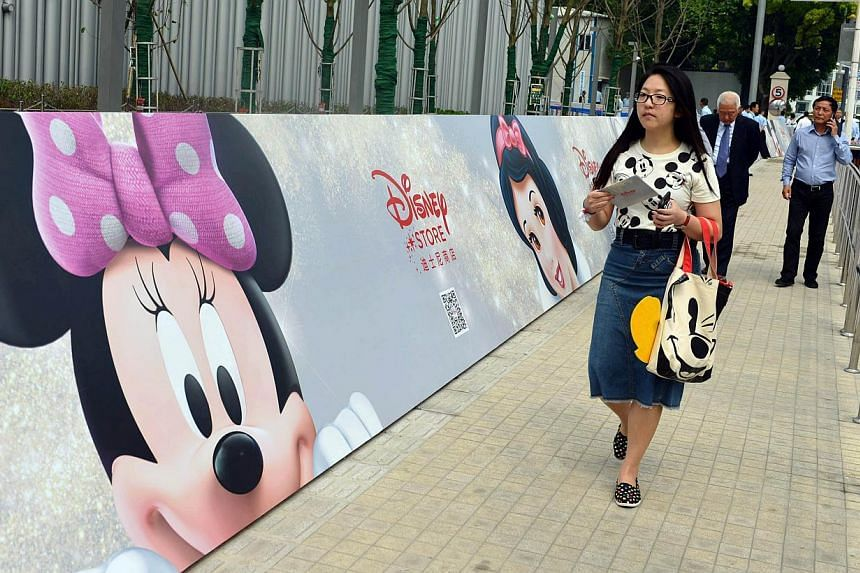 People walk past a banner of Disney animated characters outside China's first Disney flagship store at the Lujiazui financial district in Shanghai on May 20, 2015. -- PHOTO: AFP