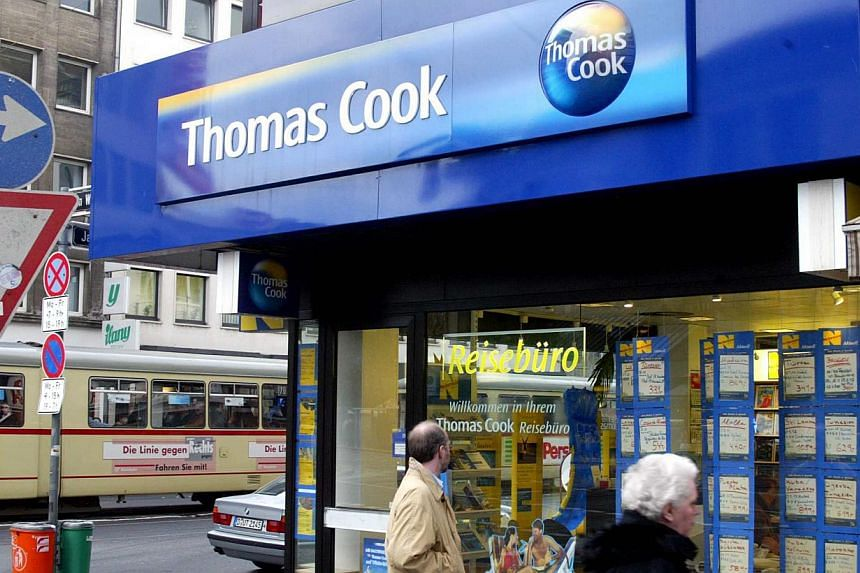 Pedestrians pass a Thomas Cook travel agency ocation in Duesseldorf, Germany on November 18, 2002. Travel firm Thomas Cook expressed regret on Wednesday for the deaths of two British children on one of its holidays in 2006, seeking to