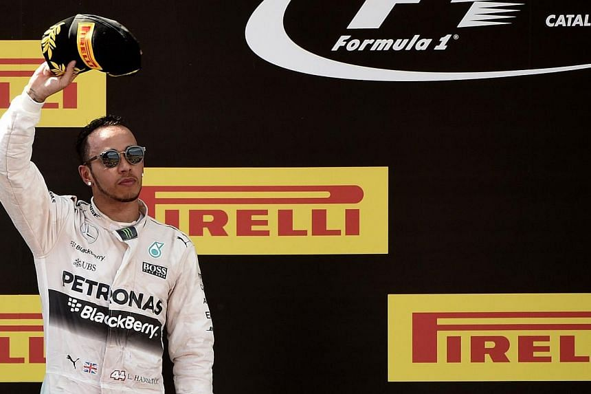 Mercedes driver Lewis Hamilton of Britain celebrates on the podium after the Spanish Formula One Grand Prix on May 10, 2015 at the Circuit de Catalunya in Montmelo on the outskirts of Barcelona. Hamilton has agreed a new three-year contract that will