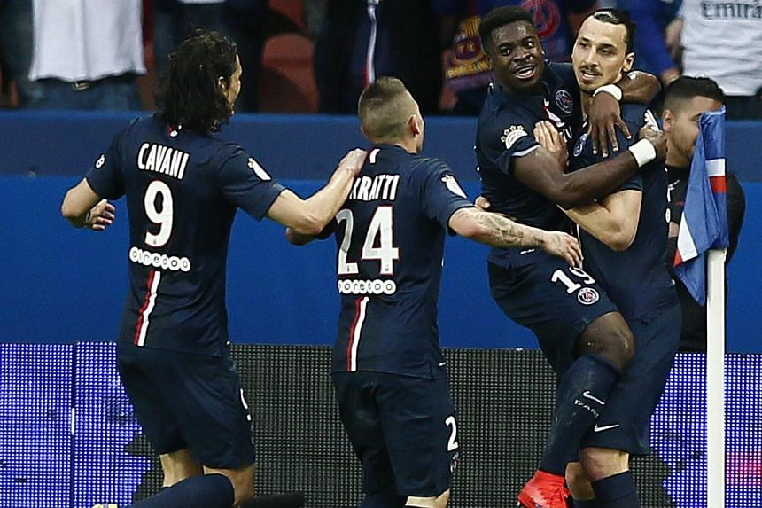 Paris St Germain's Zlatan Ibrahimovic (right) celebrates with Paris St Germain's Serge Aurier (second-right) after scoring the 2-0 goal during the French Ligue 1 soccer match between Paris Saint-Germain (PSG) and EA Guingamp at the Parc des Princes s