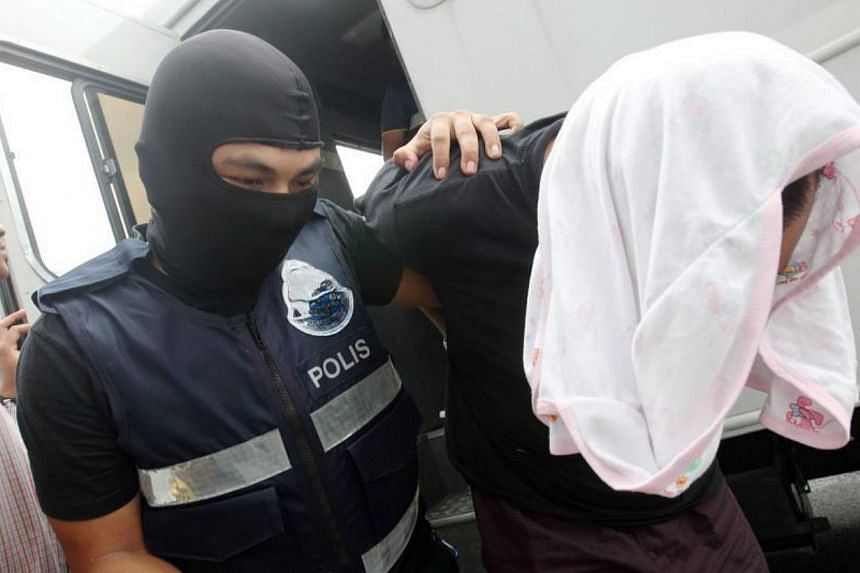 Malaysian police escorting one of six suspects arrested for being involved with terrorist activity, into Kajang court, on May 20, 2015. Five men and a teenager were charged in a Malaysian court on Wednesday with plotting terror attacks in the country