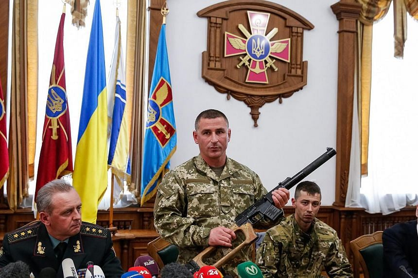 A Ukrainian soldier shows a weapon allegedly belonging to Russian servicemen captured by Ukrainian forces, during a briefing in Kiev, Ukraine on May 18, 2015. The two suspected Russian soldiers who were captured by Ukraine have been charged with invo