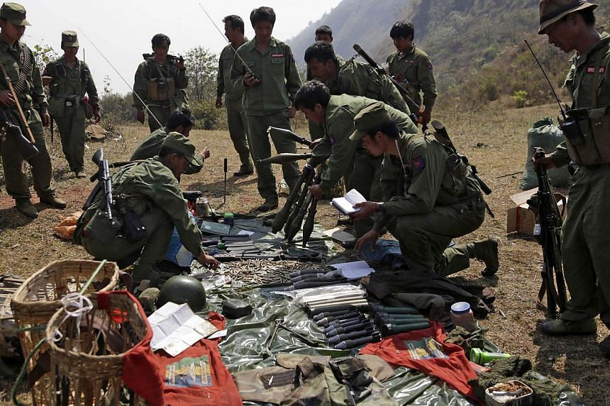 Rebel soldiers of the Myanmar National Democratic Alliance Army (MNDAA) examine weapons and ammunition at a military base in Kokang region on March 10, 2015.China on Wednesday said it had lodged a protest with Myanmar after shelling injured fiv