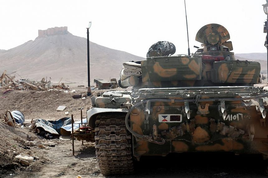 A Syrian armoured tank take up position during fightings against Islamic State in Iraq and Syria (ISIS) militants in the ancient oasis city of Palmyra, about 215km north-east of Damascus, Syria, on May 19, 2015.ISIS fighters seized around a thi