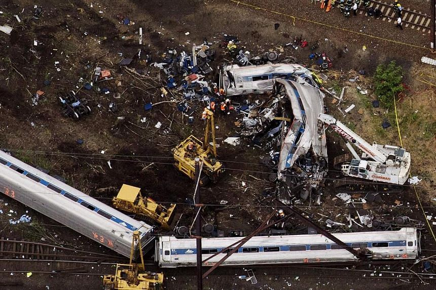 Emergency workers look through the remains of a derailed Amtrak train in Philadelphia, Pennsylvania, in this file photo taken May 13. -- PHOTO: REUTERS