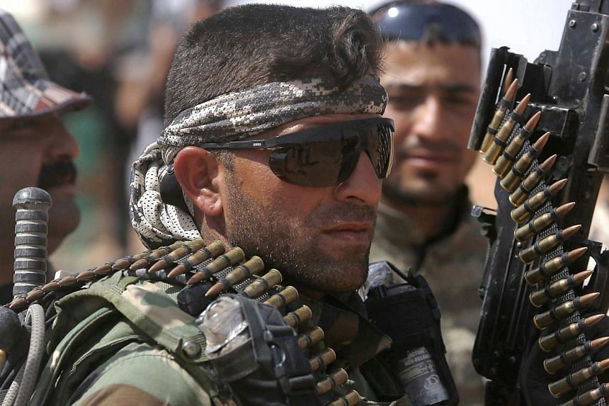 An Iraqi fighter from the Shiite Muslim Al-Abbas popular mobilisation unit holds a weapon in the area surrounding the village of Nukhayb in the embattled Anbar province west of the capital Baghdad, on Tuesday. Iraq's army and allied paramilitary forc